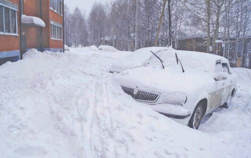 Снег с крыши упал прямо на дорожку вдоль дома и на машины